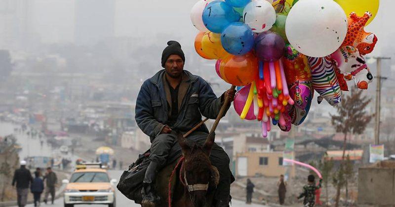 ქაბულში, ავღანეთში ვირზე შემჯდარი მამაკაცი ბუშტებს ყიდის