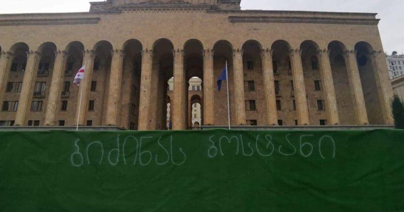 """""""ბიძინას ბოსტანი"""" - აქტივისტებმა პარლამენტთან მერიის ღობეზე წარწერა გააკეთეს"""
